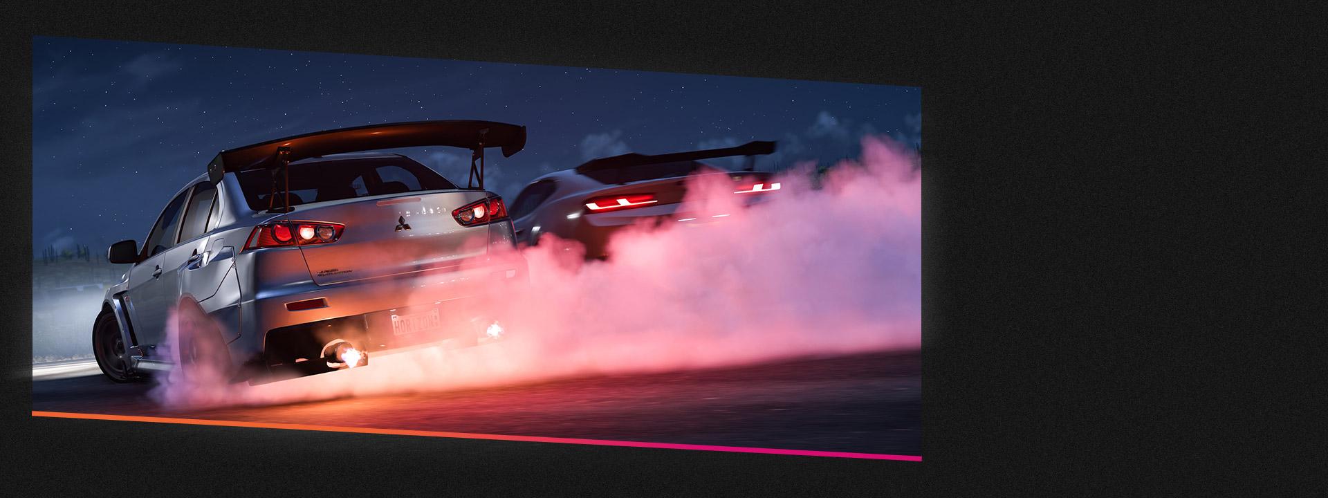 연기가 나는 타이어를 단 채 경주하는 자동차 두 대.