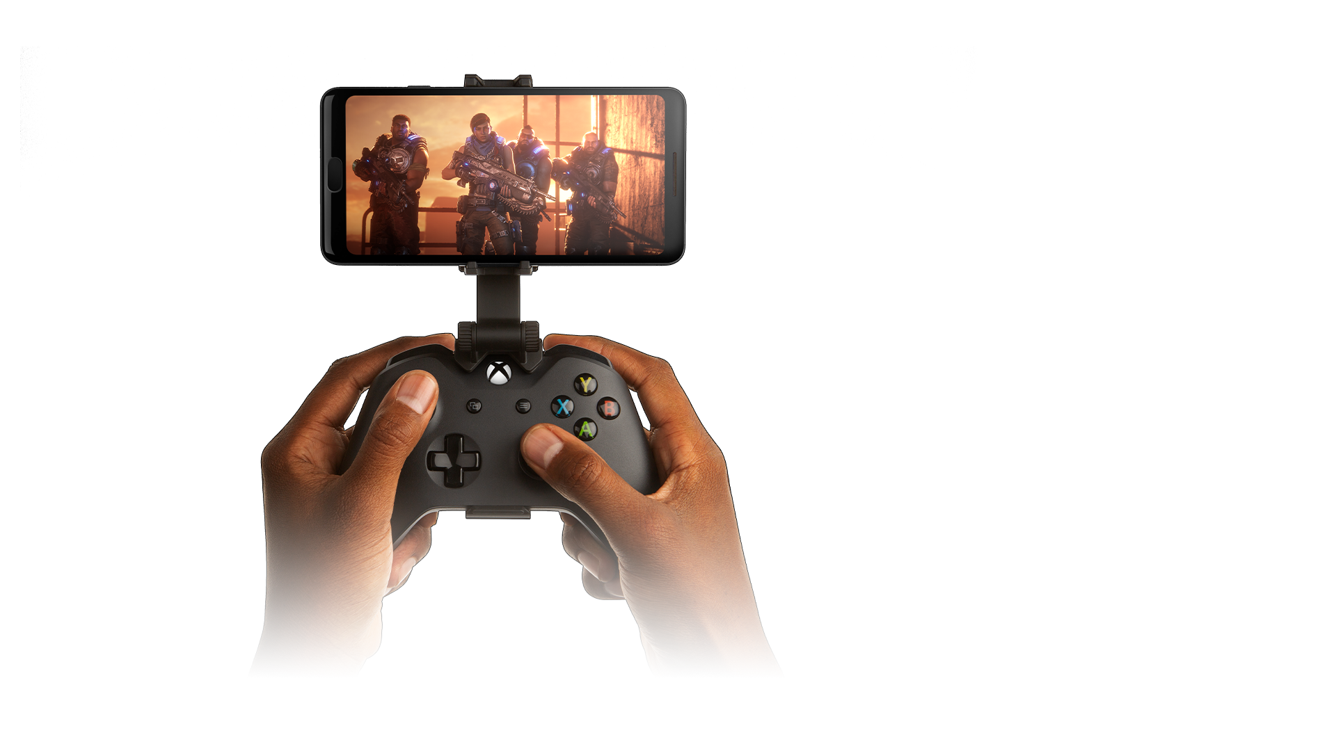 Player holding a controller with a smartphone clipped on, phone screen shows Gears 5 gameplay