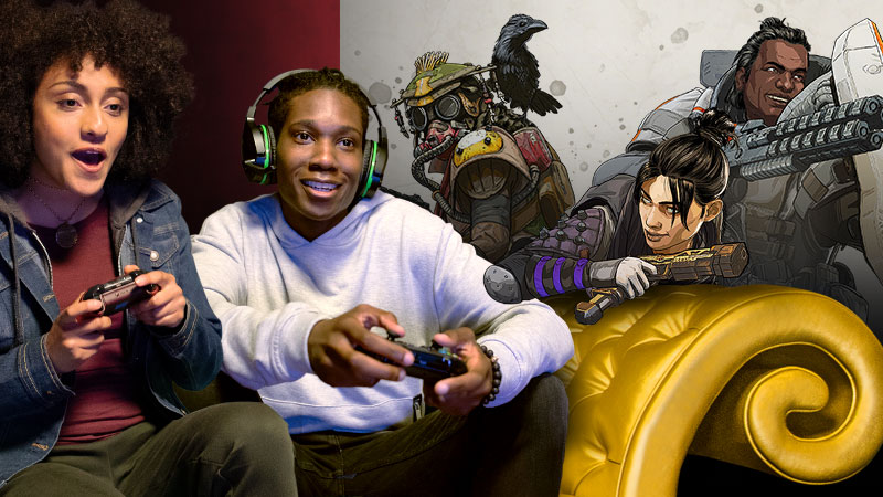 Two gamers excitedly grasp controllers on a gold couch. Characters from Apex Legends appear in the background