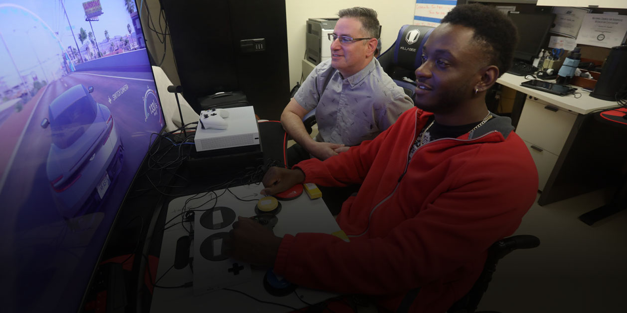 VA recreation therapist Jamie Kaplan, left, looks on as Mike Monthervil plays a game
