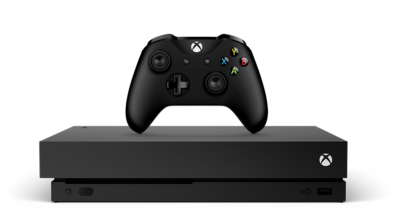 Xbox One X with a controller on top