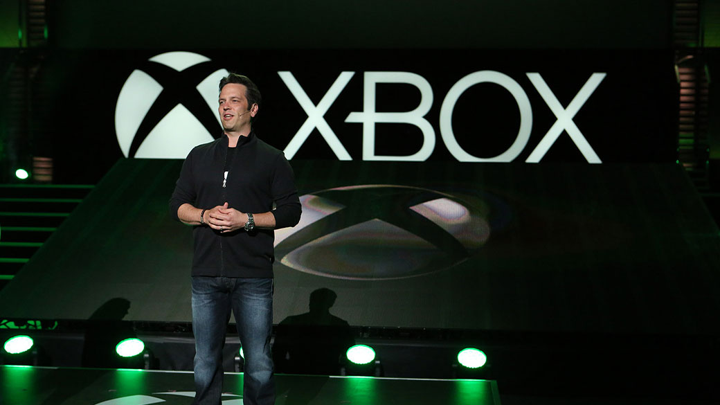 Phil Spencer, the head of Xbox, stands on a stage in front of the Xbox logo