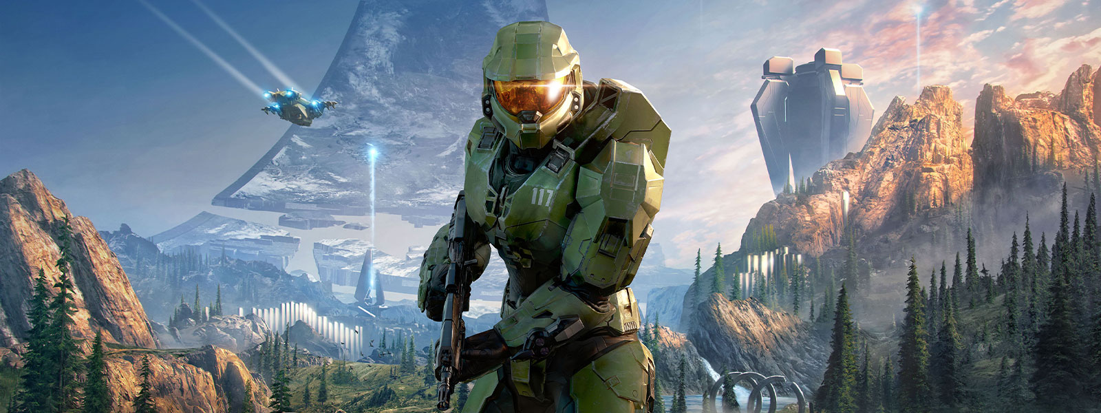 Master Chief holding an assault rifle with the ring in the background