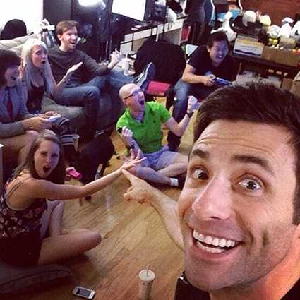 A selfie of a group of friends sitting on a couch and playing games together, submitted by 'Tedakin'