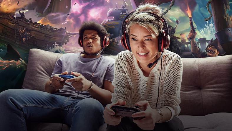 Two people wearing headsets playing Xbox One on a couch together