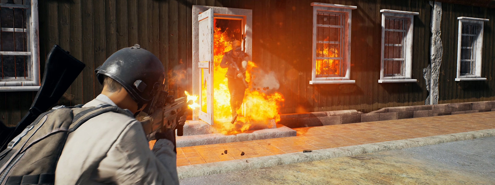 Player running out of burning building while another player is shooting at him
