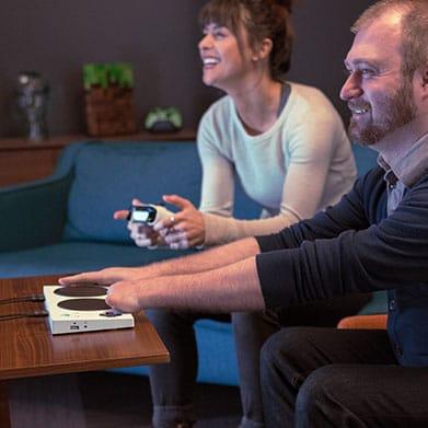 Una persona que juega a Xbox con un control adaptable Xbox contra otro jugador