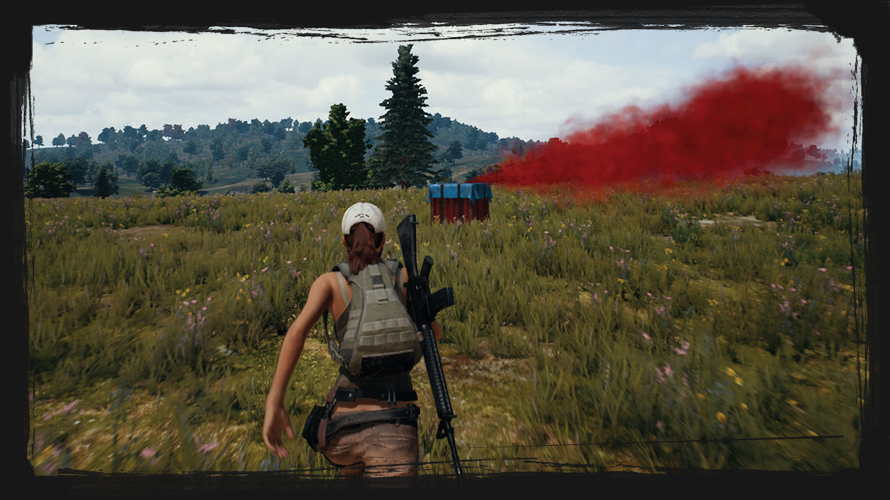 A female character runs toward a loot crate in an open field.