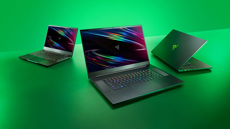 Collection of Razer laptops on a green background.