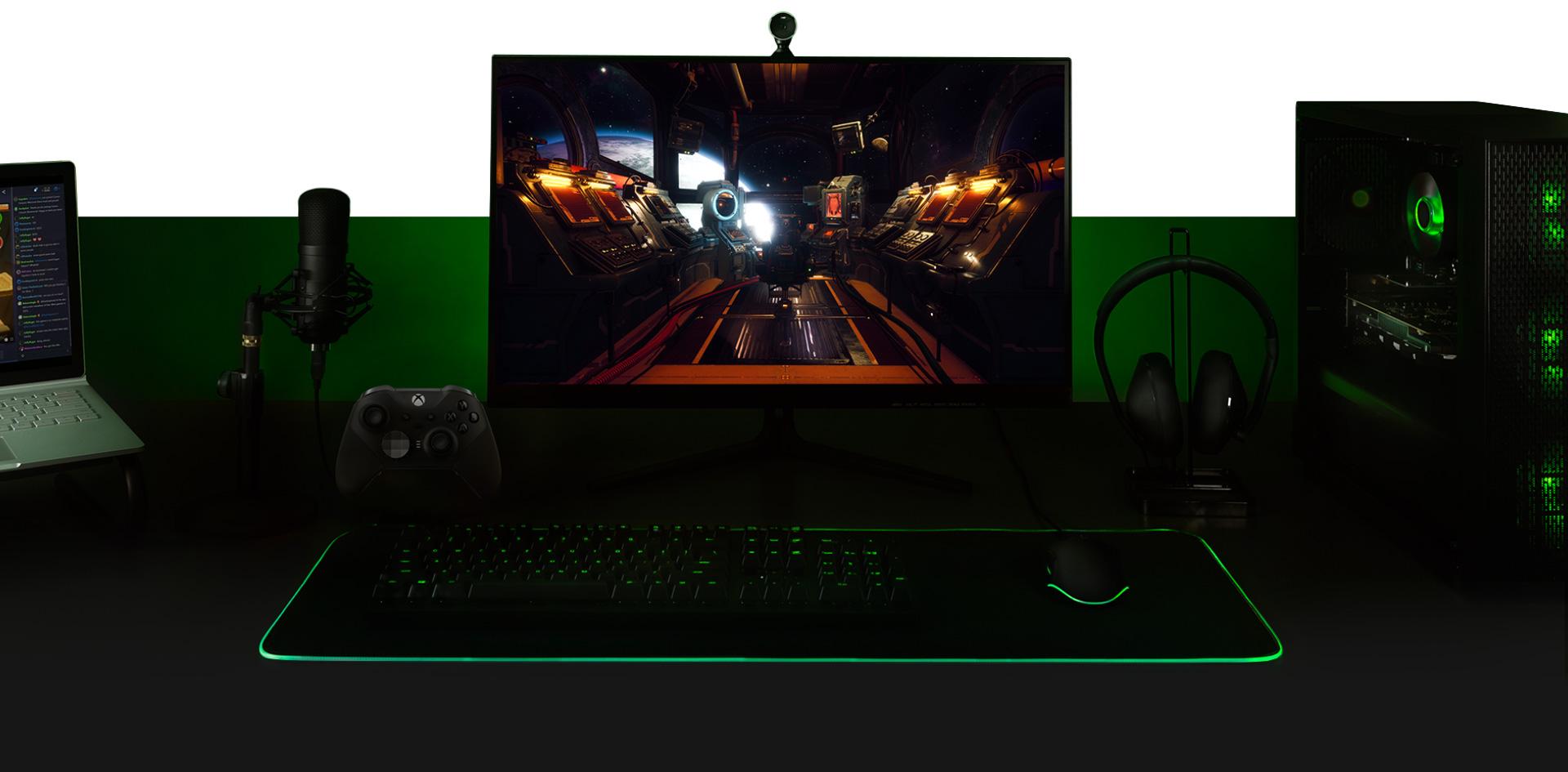 Bureau avec PC, moniteur avec écran du jeu The Outer Worlds, clavier, manette XboxOne, microphone et ordinateur portable, tous interconnectés.
