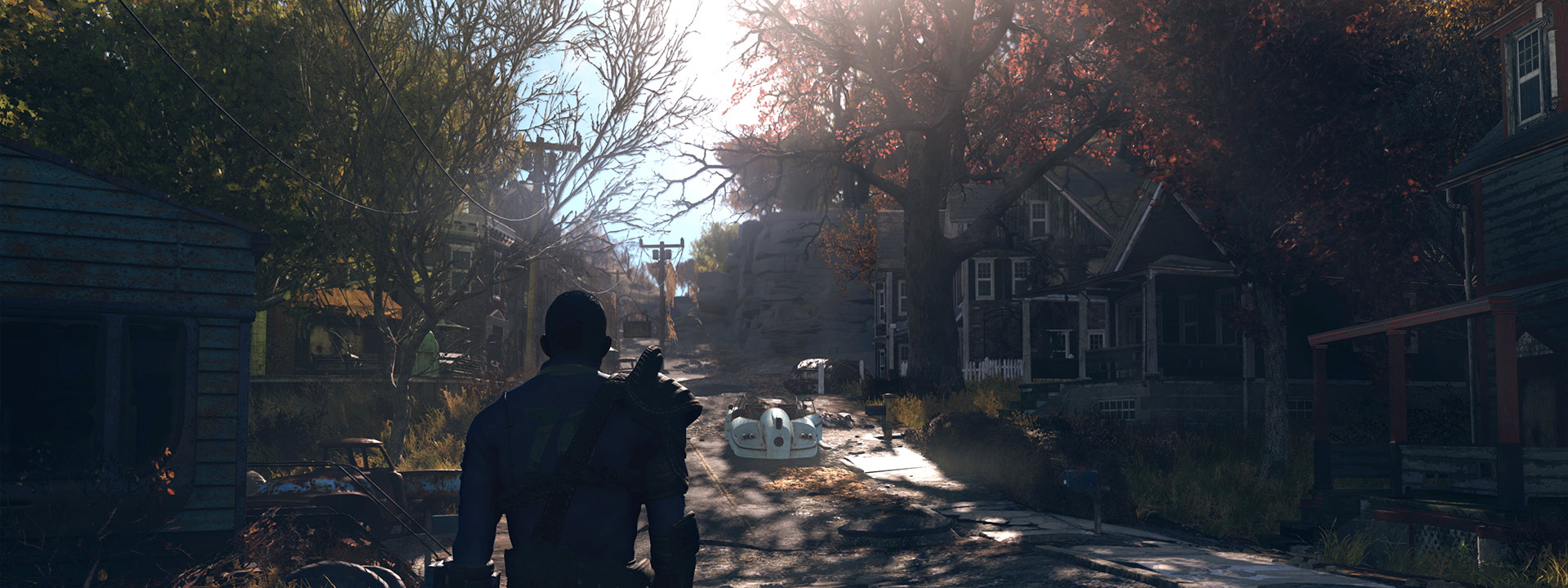 A character walks down a road through a deserted town