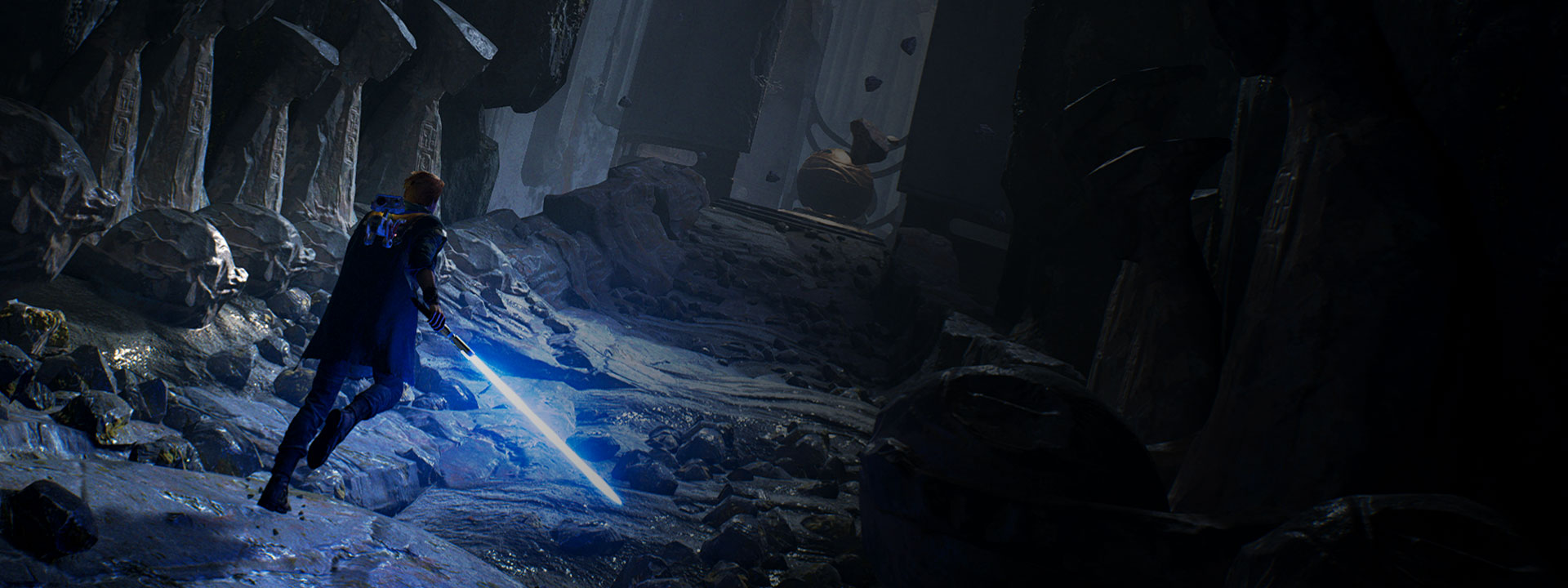 Cal Kestis readies his lightsaber as he walks through a corridor in some ruins