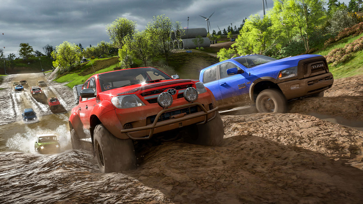 Uma picape Toyota e um Dodge Ram cortam uma pista lamacenta, na liderança