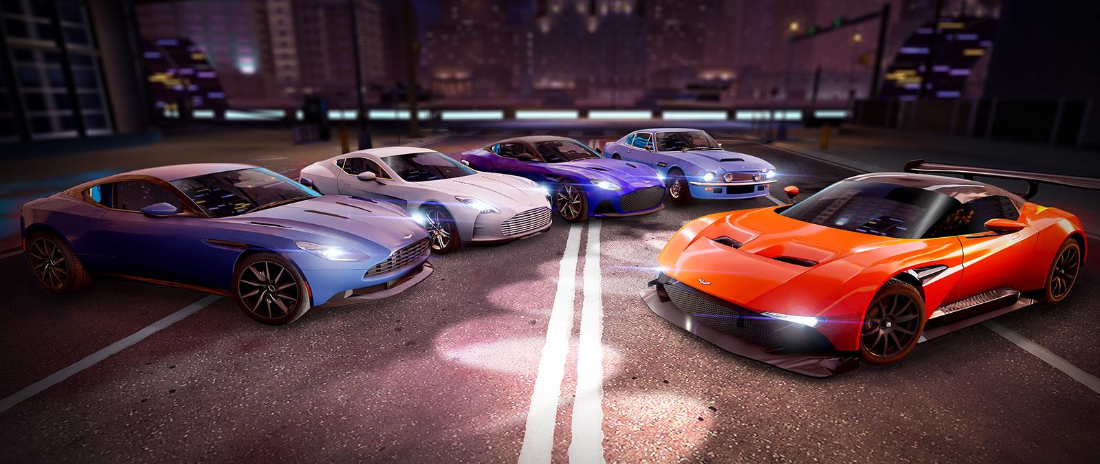 Cinq Aston Martin dans différentes couleurs alignées sur une rue de la ville