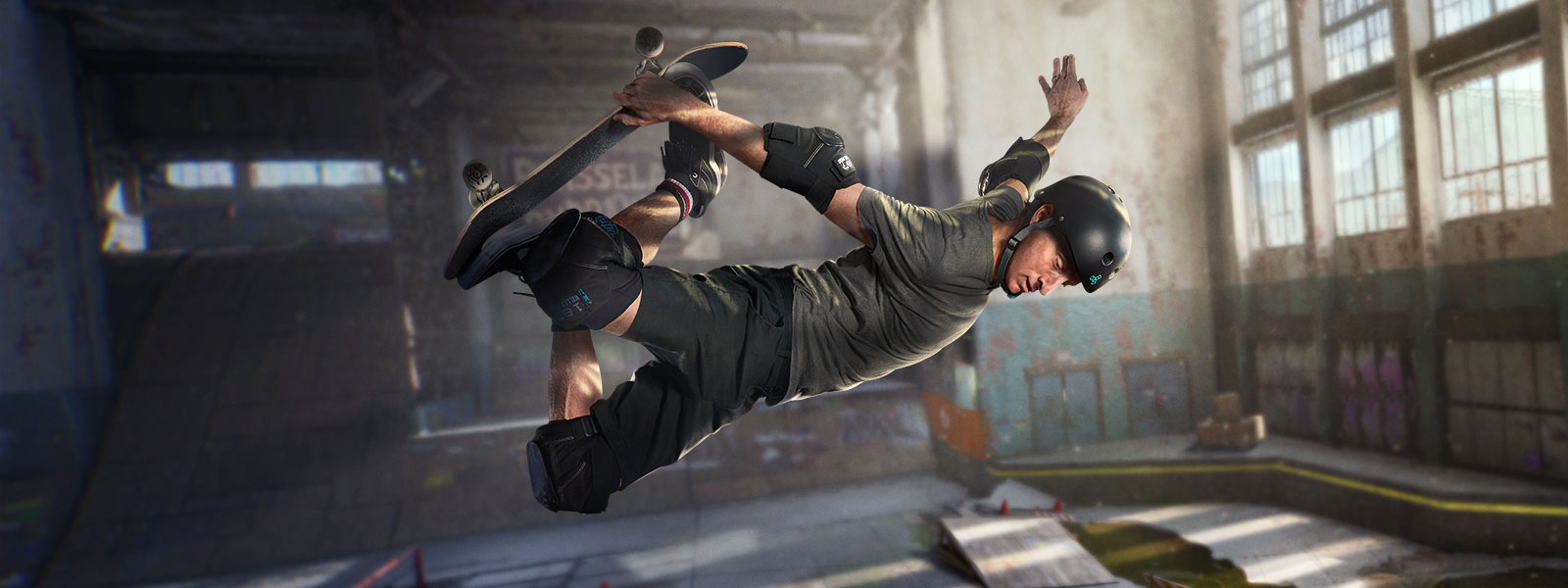 Tony Hawk rides a skateboard in a warehouse.