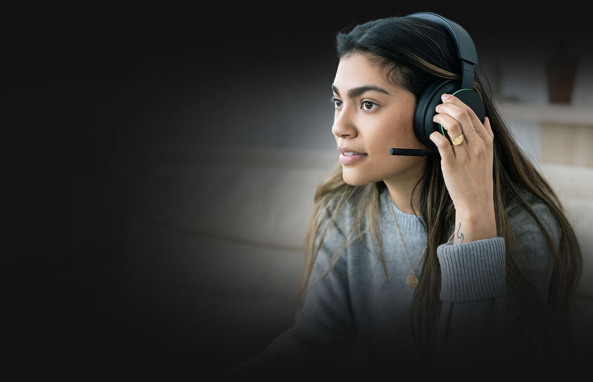 Uma mulher a ajustar o volume utilizando os botões das almofadas dos Auscultadores Sem Fios Xbox.