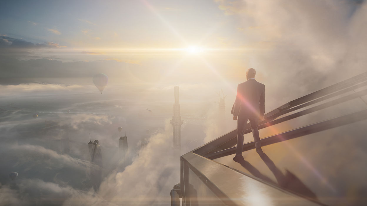 Agent 47 stands on the roof of a building looking below through the clouds at other buildings