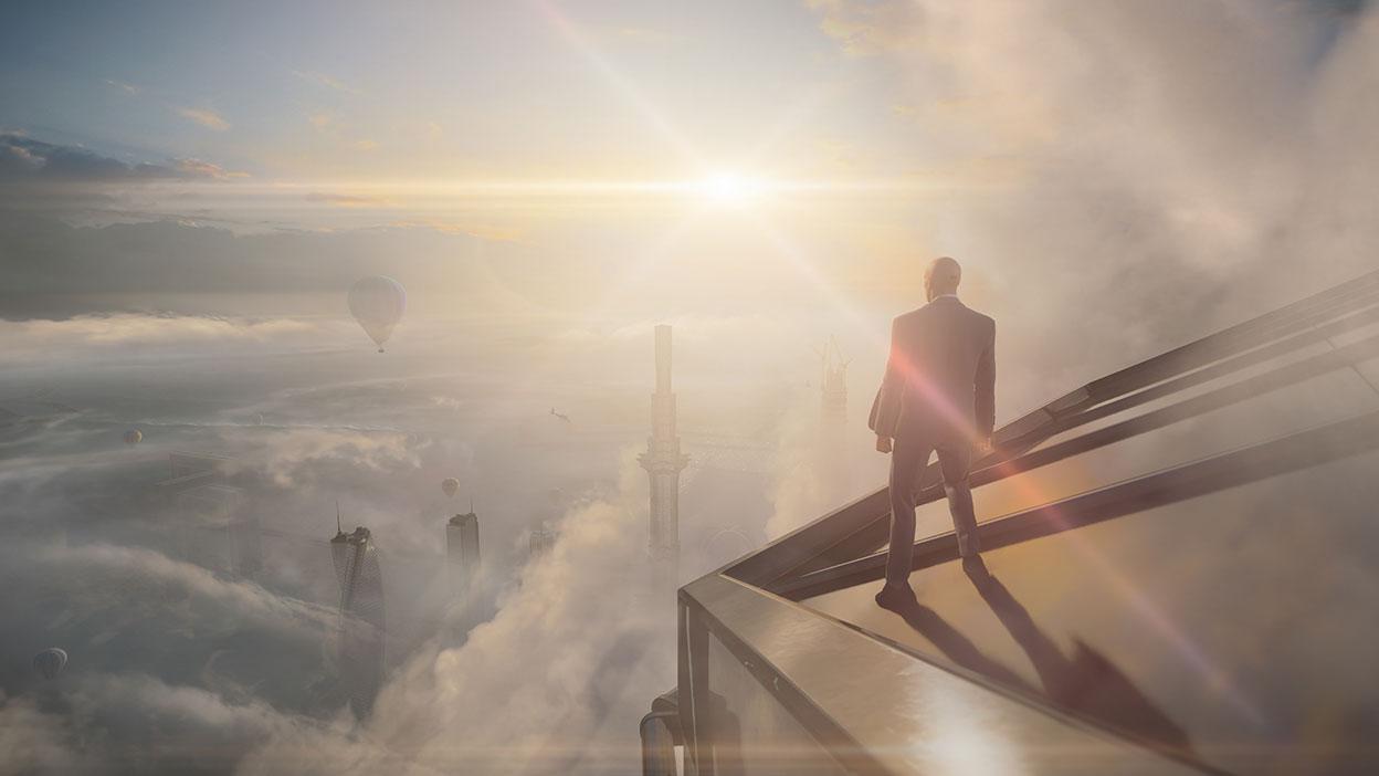 L'agent 47 se tient sur le toit d'un bâtiment et regarde d'autres bâtiments dessous à travers les nuages