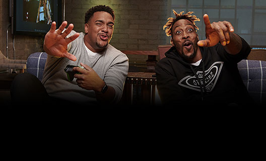 Rukari Austin and Dwight Howard react enthusiastically to something off-screen while holding Xbox One controllers.