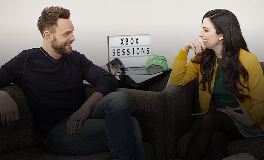 Joel McHale sits on a couch talking to host Marissa Roberto