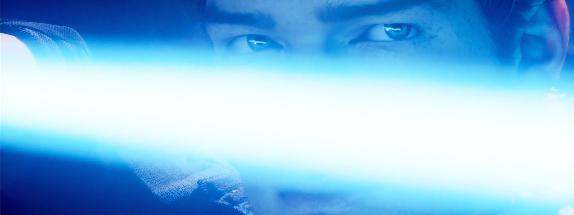 Close up of Cal Kestis holding a lightsaber in front of his face