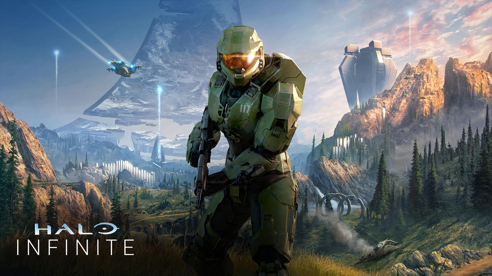 Master Chief faces forward in a lush valley with a broken Halo ring behind him