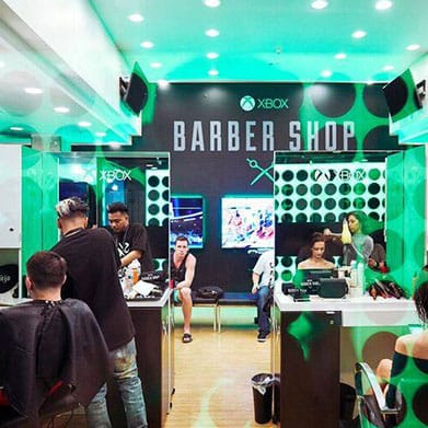 People getting a haircut at the Xbox barber shop booth