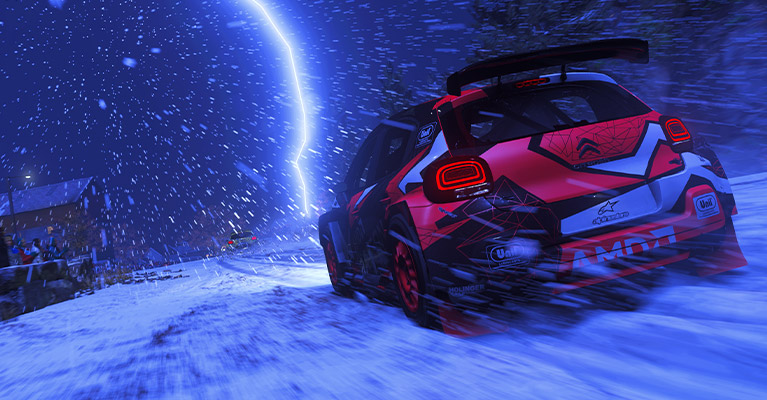 A Citroen rally car powers forward through a snow swept village road in front of a line of spectators. Lightning strikes in the distance as snow lowers visibility.