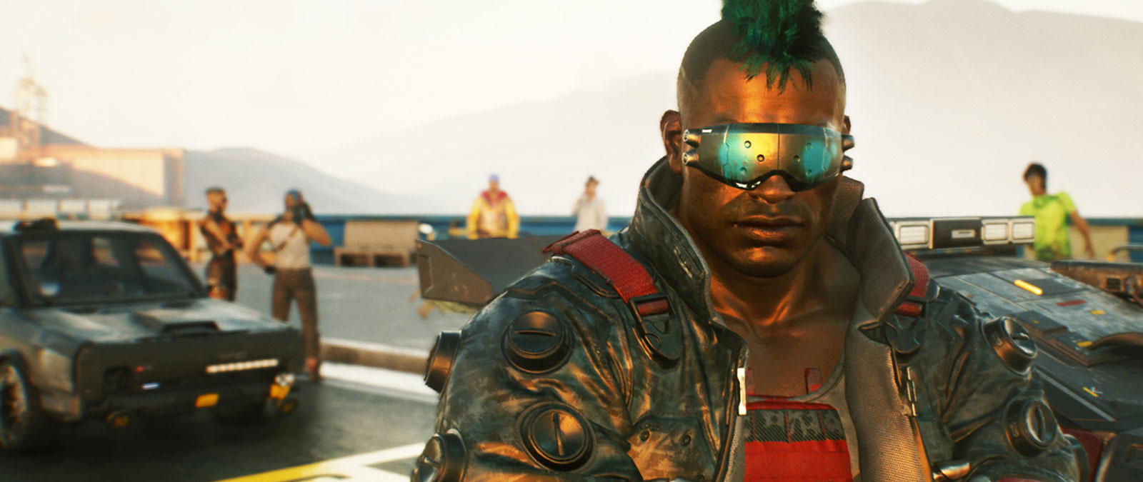 A man with a green mohawk and cyber goggles stands on the docks