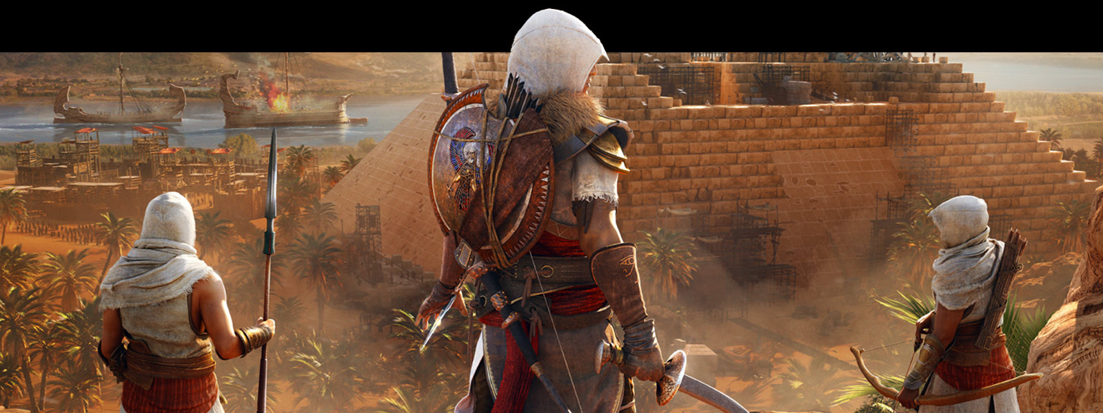 Back view of Bayek and two other assassin's standing in front of a pyramid