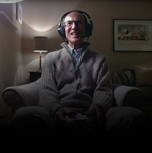 An elderly man wearing a gaming headset enjoys playing an Xbox game