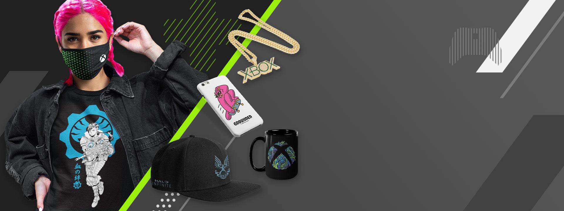 Una modella con capelli rosa e una mascherina Xbox insieme a una catenina dorata, una custodia per telefono, un cappellino e una tazza con il logo di Xbox