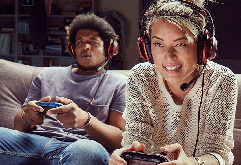 Two people wearing headsets playing Xbox games on a couch