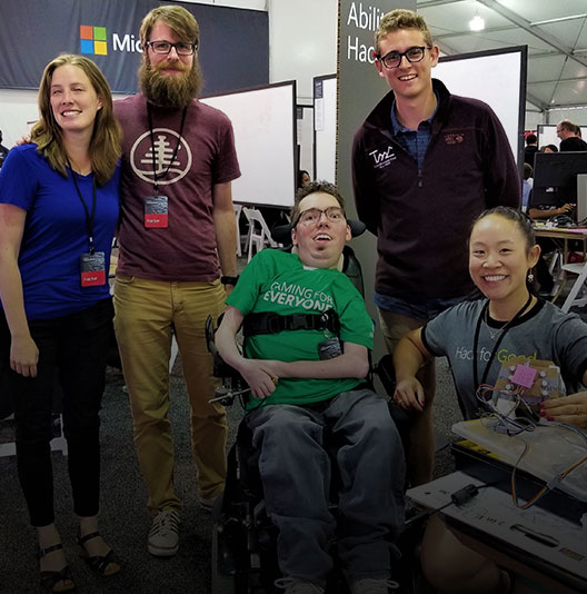 Inside the Hackathon tent, a team of five researchers, designers and engineers pose with a prototype, all smiles.
