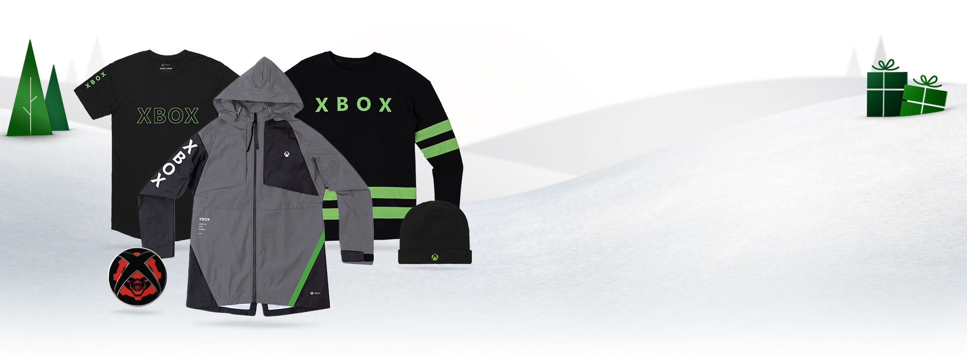 An Xbox tshirt, long sleeve, jacket, and beanie in front of a snowy background with trees and presents