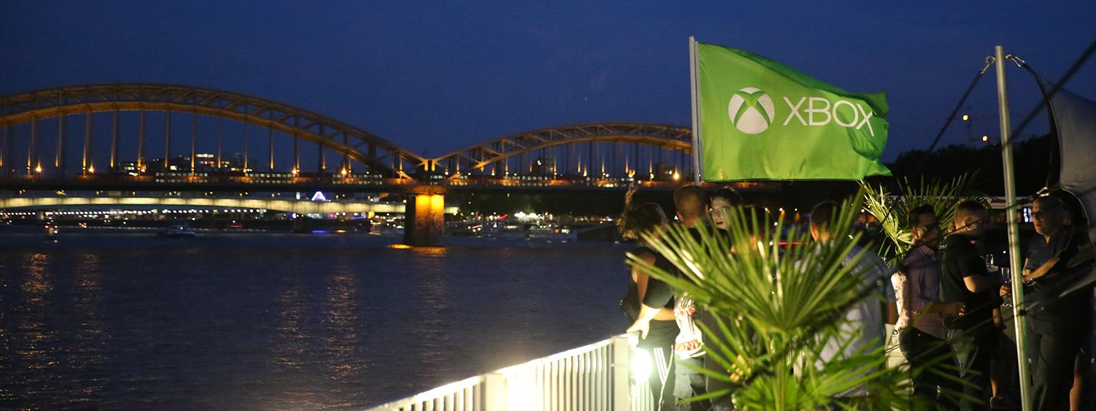 Nächtliche Szene von Menschen, die unter einer Xbox-Fahne plaudern, mit der Hohenzollernbrücke im Hintergrund
