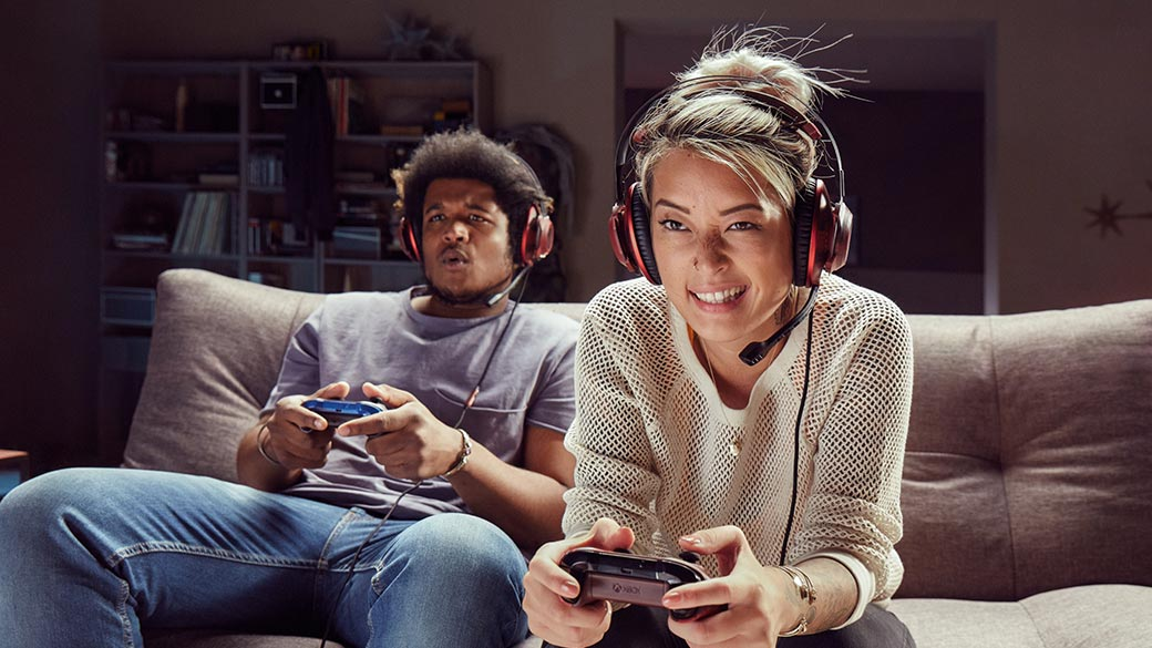 Man and woman seated on a couch playing video games