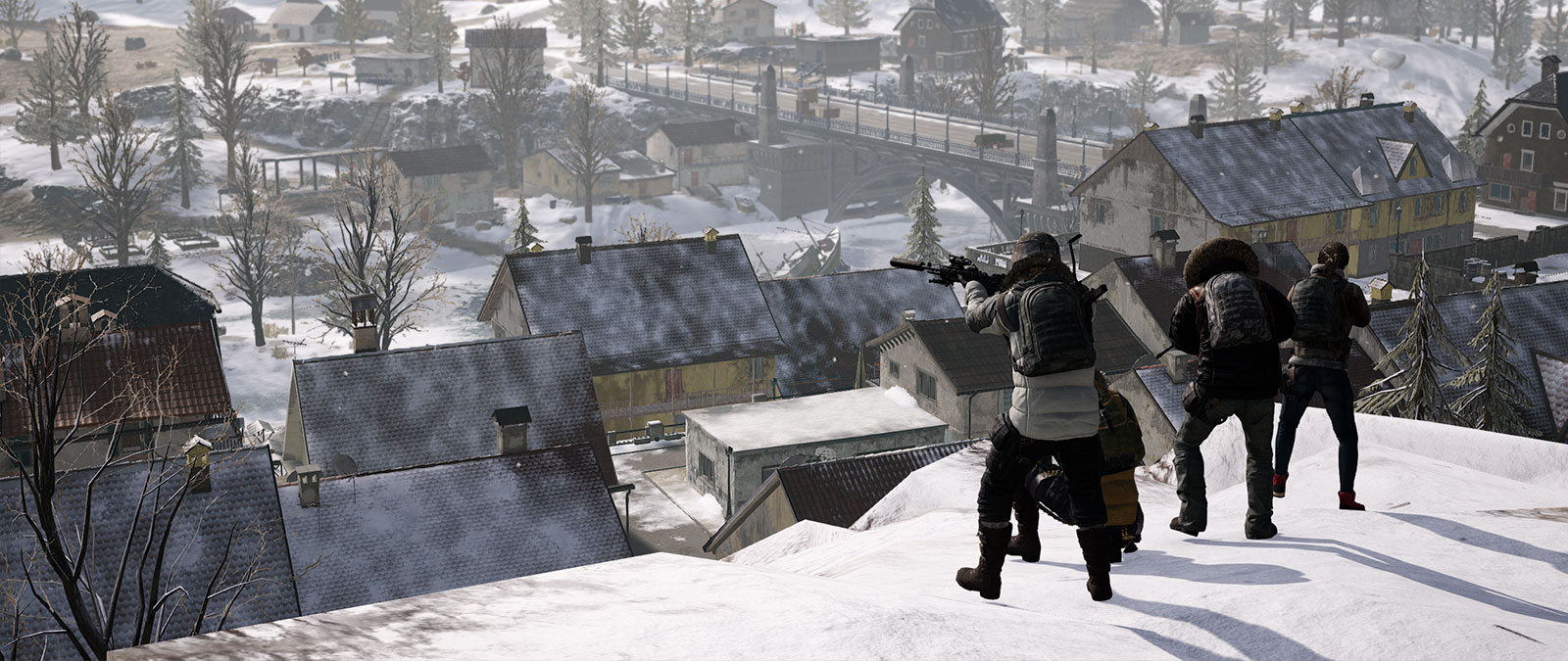 4 players stand on a snow covered hill while looking down at a town full of houses.