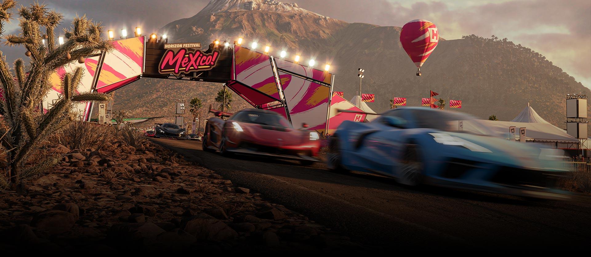 Caros do Forza Horizon 5 se movendo rápido por um Horizon Festival Mexico! Linha de chegada em um deserto com um balão de ar quente perto de uma montanha.