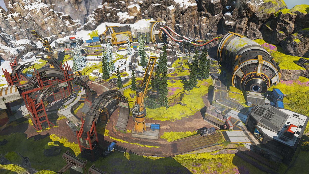 En stor arena ved siden af et sneklædt bjerg med træer og industribygninger.