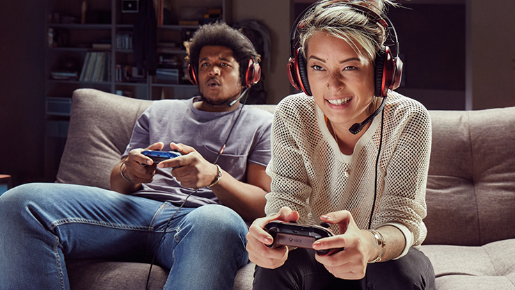Two people holding Xbox controllers and playing multiplayer games together.