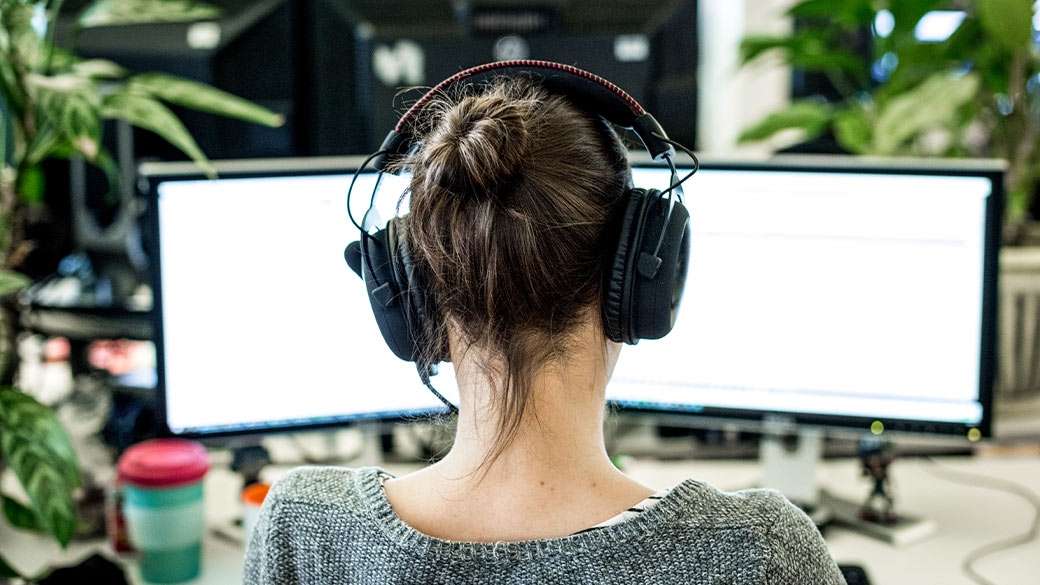 Woman with headphones sitting in front of two computer screens