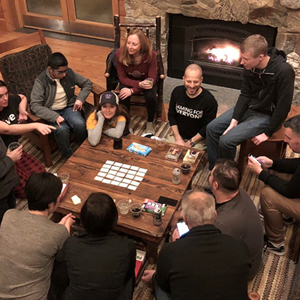 A group of friends huddled around a table and playing games, submitted by 'Deirdre206'