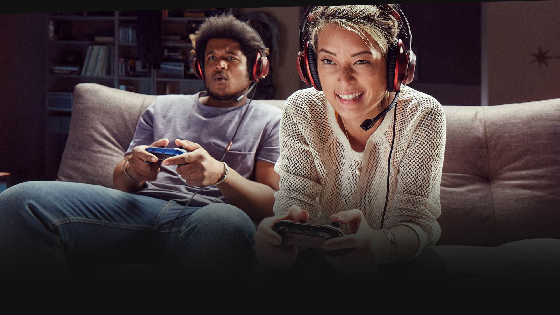 Two people wearing headsets playing Xbox one on a sofa