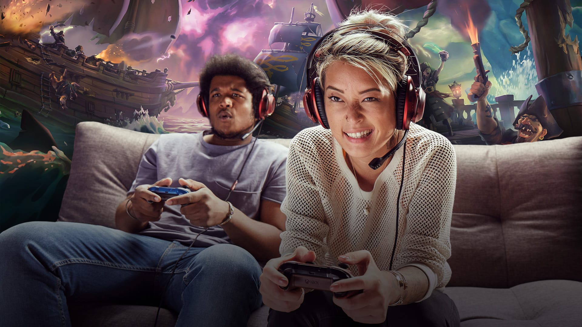 Two people wearing headsets playing Sea of Thieves on a sofa