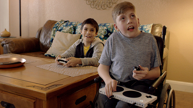 Owen uses the Xbox Adaptive Controller to play a game with his friend.