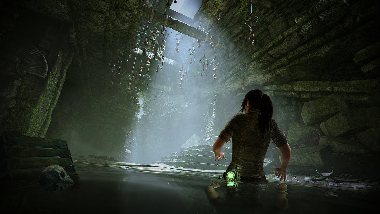 Lara Croft wades through water in a dark tomb with bones hanging from the ceiling