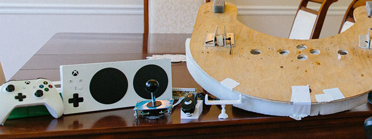 The components of Spencer's custom adaptive controller set-up are displayed on a table.