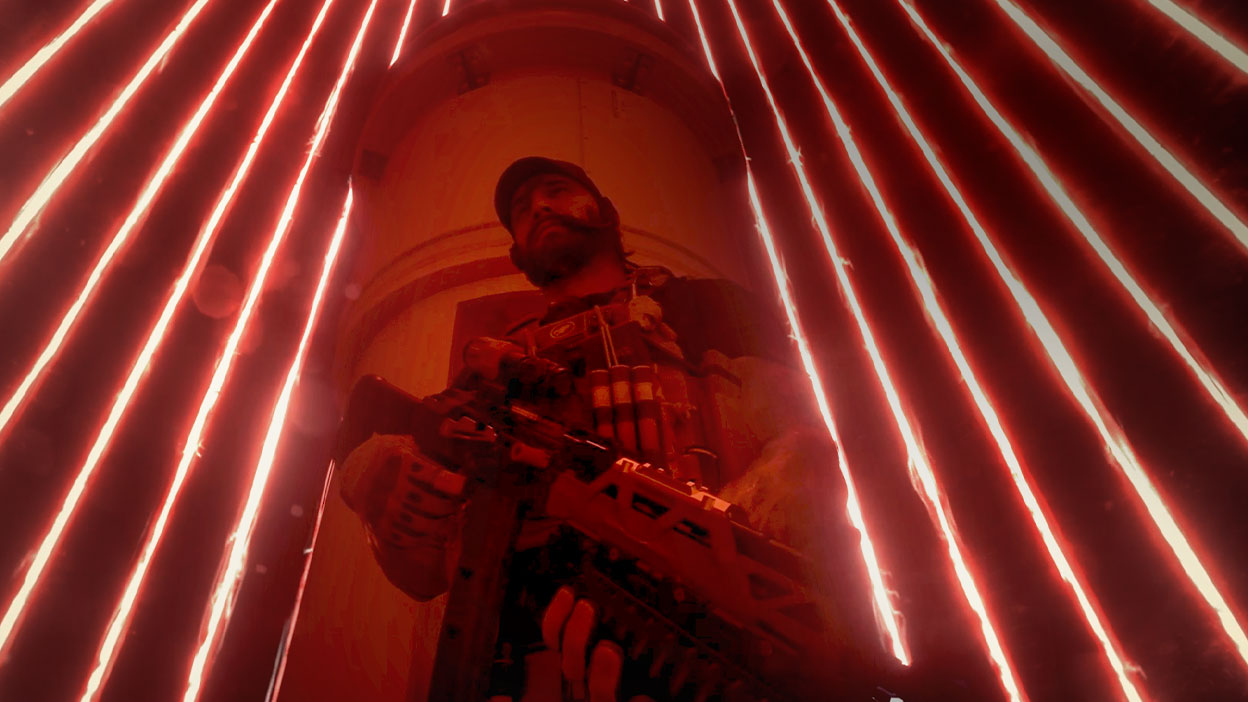 A man holding a gun stands in the centre of a cage made of lasers