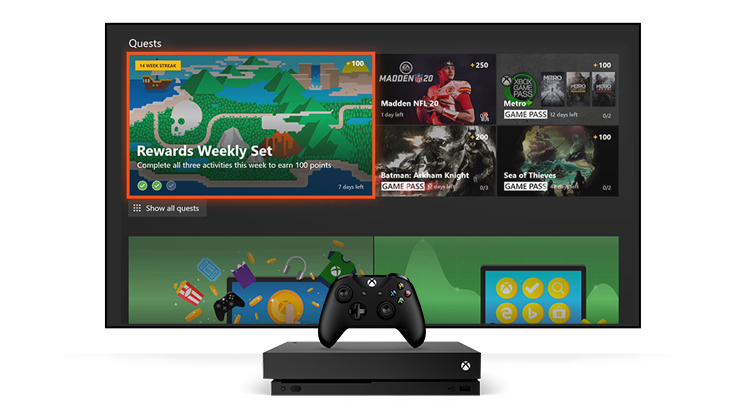 An Xbox One X in front of a console dashboard showing the Microsoft Rewards app.